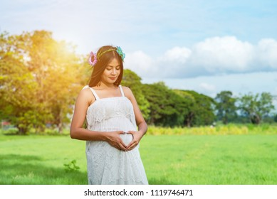 Pregnant Asian woman posing in the park