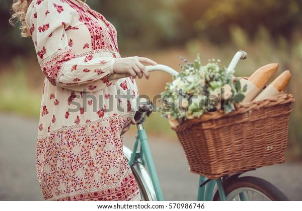 La barriga preñada contra el acercamiento natural. Niña embarazada retro estilo francés con bicicleta en una carretera forestal. Hermoso concepto de embarazo. Mujer feliz rubia con el pelo rizado en el fondo de la naturaleza.