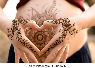 Pregnant belly with mehendi henna tattoo on the beach, cropped image, hands in heart shape over pregnant tummy. Motherhood concept, happy maternity