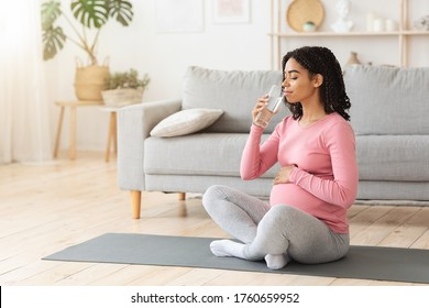 Pregnant black woman drinking water during exercising at home, healthy pregnancy concept, empty space