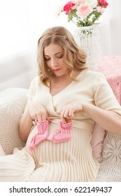 Pregnant blond  woman sits on the couch at home with pink baby's bootees. Modern interiori pastel colors. Professional style and make-up