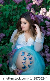 Pregnant brunette in a blue boudoir dress near the lilac bushes with butterflies on the stomach.  Maternity concept