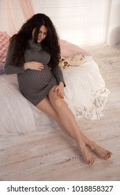 pregnant brunette in a knitted dress