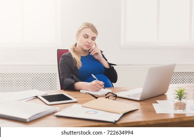Pregnant business lady at work talking on phone. Worried expectant businesswoman sitting at her working place in office, copy space