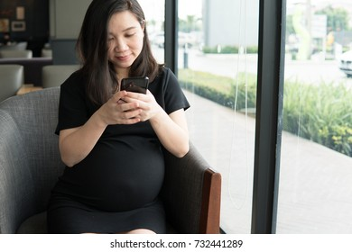 pregnant business woman use mobile phone chatting with her clients at coffee shop. pregnant working concept