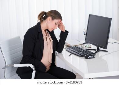 Pregnant Businesswoman Having Headache Sitting In A Chair At Desk