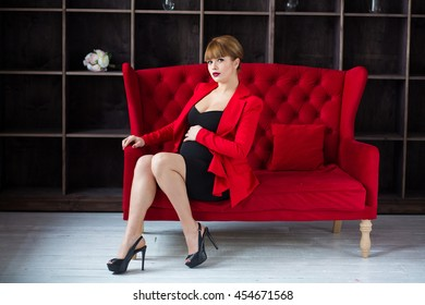 pregnant businesswoman wearing a black dress and a red jacket