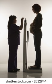 Pregnant Caucasian mid-adult woman being weighed by nurse.