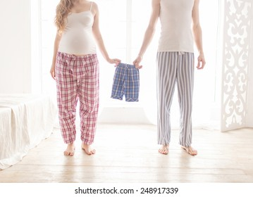 pregnant couple holding children's pajamas in the morning in the bedroom