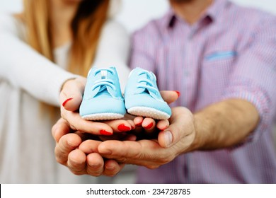 Pregnant couple holding their future baby boots