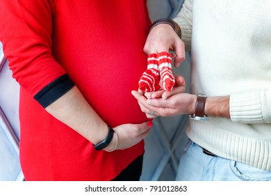 Pregnant couple hugging woman belly, close up. Mum and dad holding newborn shoes in hands