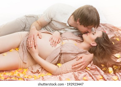 Pregnant couple lying kissing and carressing belly on beige fabrics
