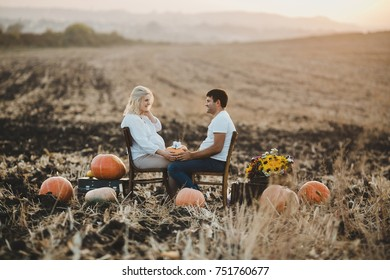 Pregnant couple sits on old suitcases with pumpkins on the field