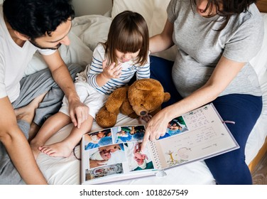 Pregnant family looking through a family photo album