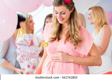 Pregnant girl celebrating baby shower party with friends, showing her baby belly