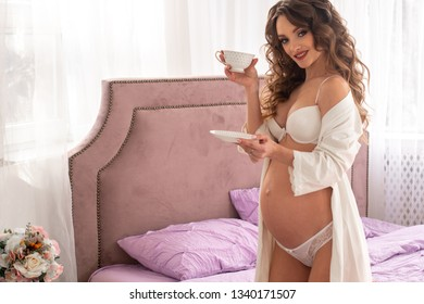 pregnant girl drinks coffee in bed