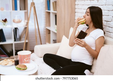 Pregnant girl eating a hamburger and chocolate sitting on the couch. She's at home. She is hungry.