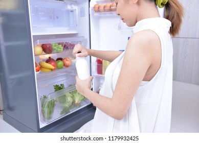 Pregnant girl find something to eat in refrigerator. And she found a bottle of milk. In the refrigerator have a lot vegetables and fruits. It's have a lot nutrient important for fetus too much.