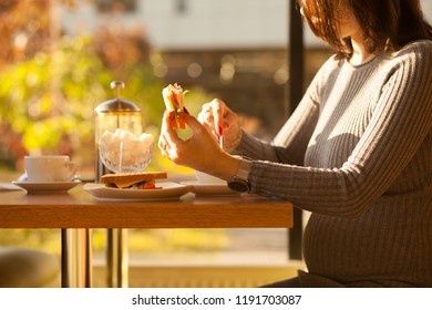 Pregnant girl has lunch in a cafe
