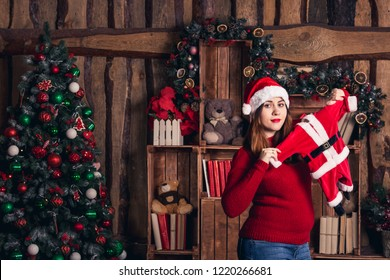 A pregnant girl is holding a Christmas costume for the baby