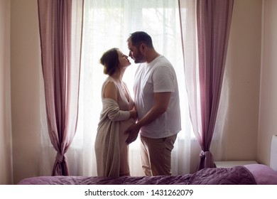 pregnant girl in a nightie with her husband in a white t-shirt stands against the window of the house and hold hands