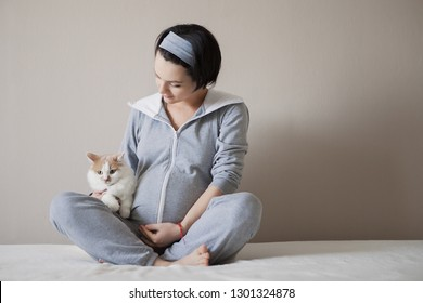 pregnant girl is resting at home in a gray suit, next to a pet, a cat. Motherhood