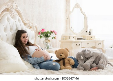 Pregnant girl resting on the bed in the bedroom with toys on the window background