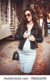 Pregnant girl walking in the park, beautiful happy woman