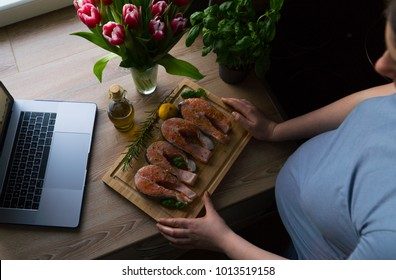 The pregnant girl is watching the online course and preparing salmon with rosemary and lemon for lunch. On the table are fresh tulip flowers. Top view