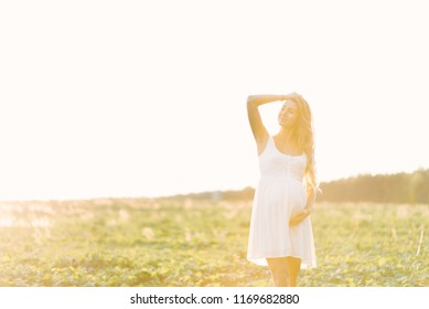 pregnant girl in white dress at sunset