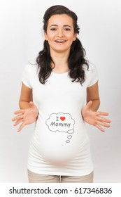 A pregnant girl in a white T-shirt, with a funny picture.