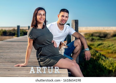Pregnant happy couple with small dog poses near the marshlands.