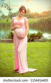 Pregnant happy Woman touching her belly. Full length Pregnant beauty young mother outdoor portrait, caressing her belly and smiling. Healthy Pregnancy concept, brunette expectant female in summer park