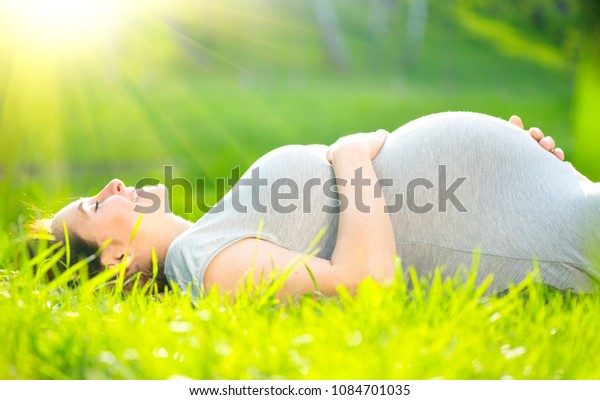 Pregnant happy Woman touching her belly. Pregnant middle aged mother in spring meadow lying on green grass, enjoying nature, caressing belly, smiling. Healthy Pregnancy concept, expectant mom outdoors