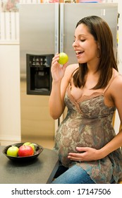 Pregnant Hispanic woman eating a green apple in her kitchen. Focus is on woman's face. The background is blurred.