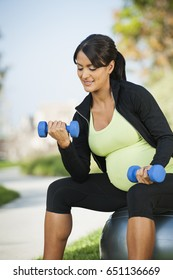 Pregnant Hispanic woman lifting weights outdoors