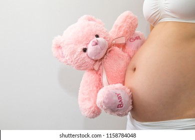 Pregnant lady announcing she is pregnant of a baby girl by holding a pink teddy bear on her belly