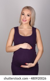 Pregnant lady in a dress hugging her tummy. Close up. Gray background