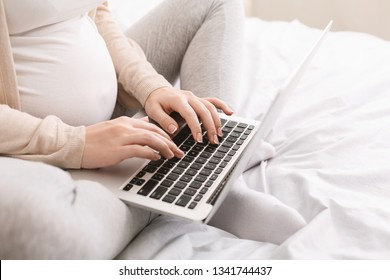 Pregnant lady using laptop, working in homeoffice or taking online education courses during maternity leave, closeup