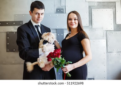 Pregnant loving couple holsing cat looking at camera. Elegant pregnant woman.