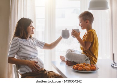 Pregnant mom with kid drinking tea together in the kitchen. Mother with son sharing good emotions while having breakfast at home.