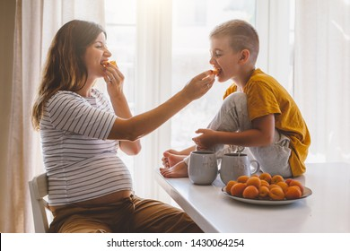 Pregnant mom with kid eating fruits together in the kitchen. Mother with son sharing good emotions while having breakfast at home.