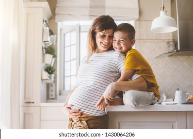 Pregnant mom with kid playing together and laughing in the kitchen. Mother with son sharing good emotions while having breakfast at home.