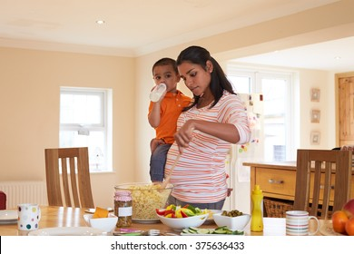 Pregnant Mother Carrying Son Whilst Making Salad In Kitchen