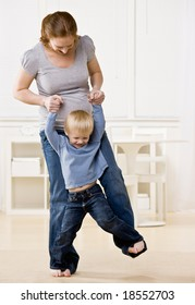 Pregnant mother dances playfully with her son on her feet