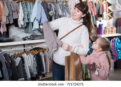 Pregnant mother and daughter looked after clothes for future brother in the children's clothing store
