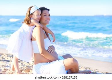 Pregnant mother and daughter on the beach together hug sitting on sand
