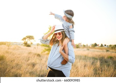 515108b172ae2 Pregnant mother and daughter wear matching jean clothes and enjoy the summer