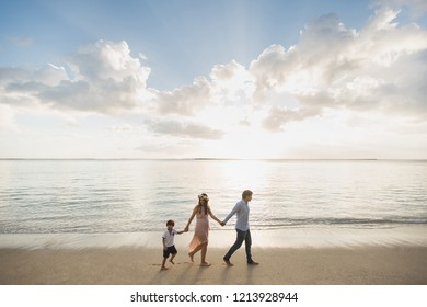 Pregnant mother, father and son walking on the beach