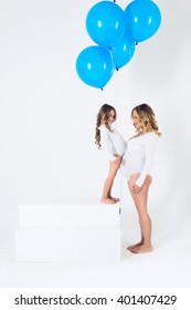 pregnant mother with her daughter with blue balloon